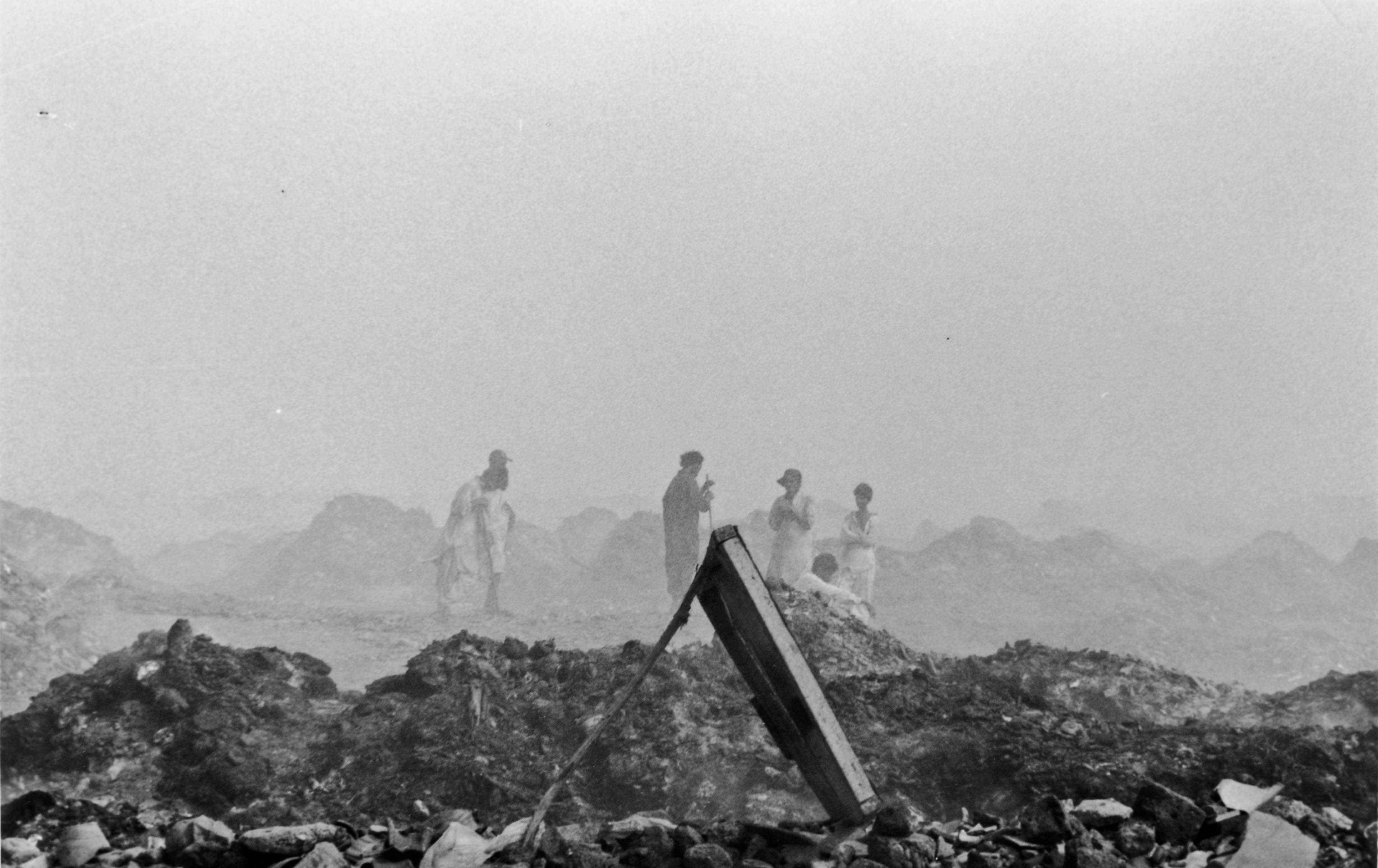 workers take a break from sifting through landfill